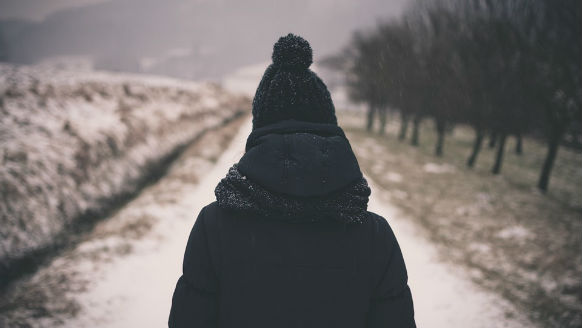 women in wither coat walking down path