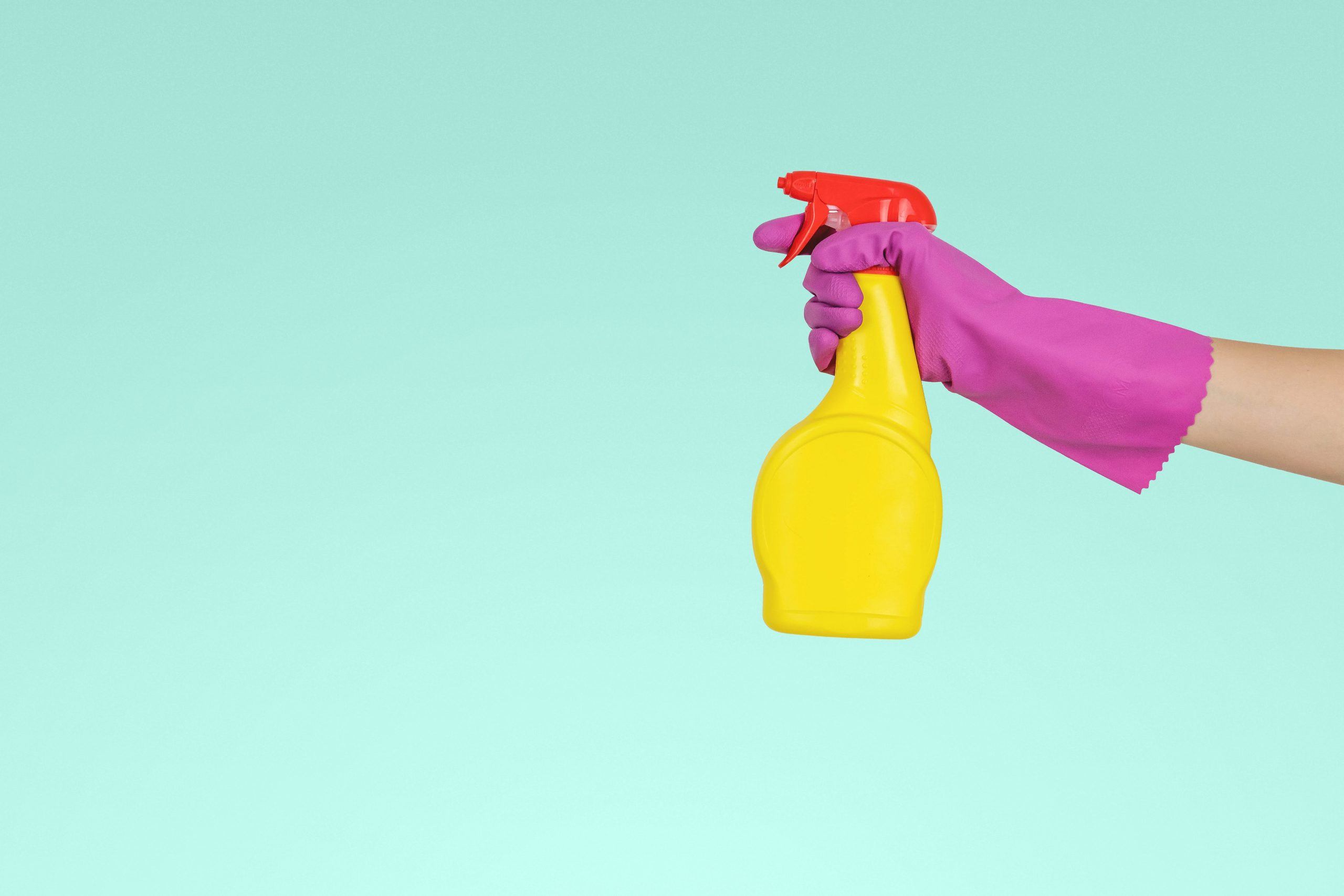 Hand in cleaning gloves, disinfecting a home with spray